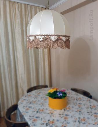 Ретро-абажур с бахромой висит над столом.